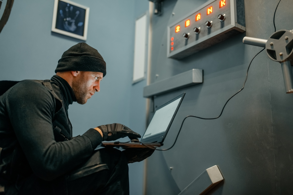 Robber braking into bank using laptop