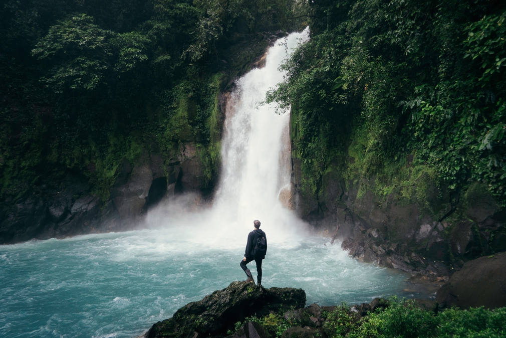 young man exploring a waterfall