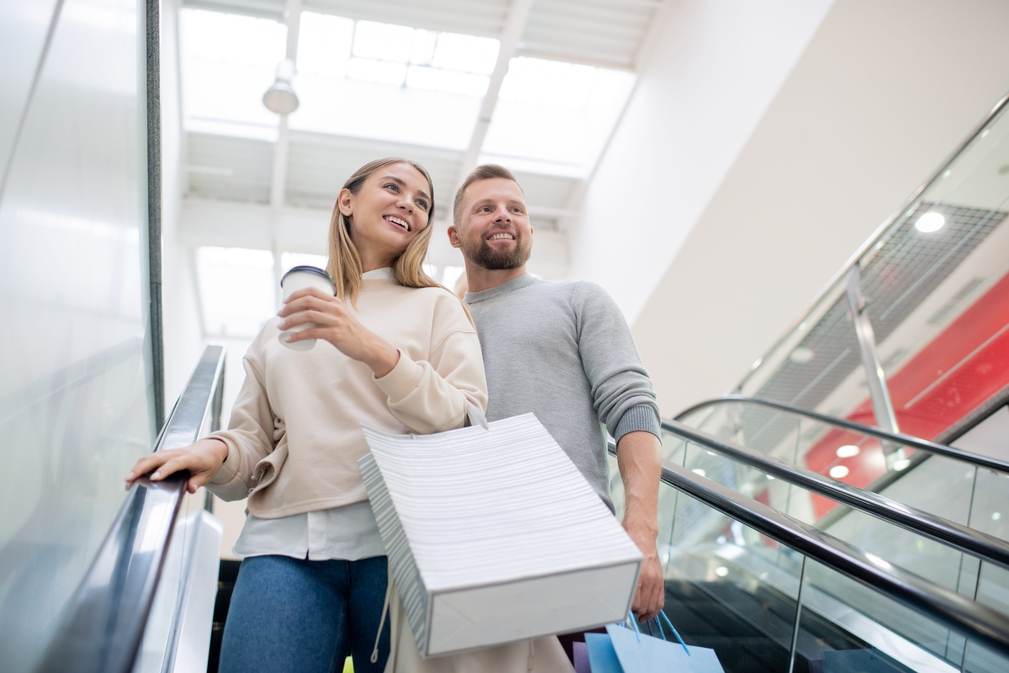 Couple with shopping bags on escalator