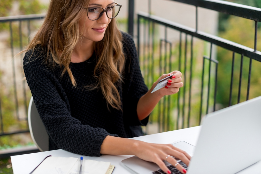 Woman wearing Glasses on laptop with credit card