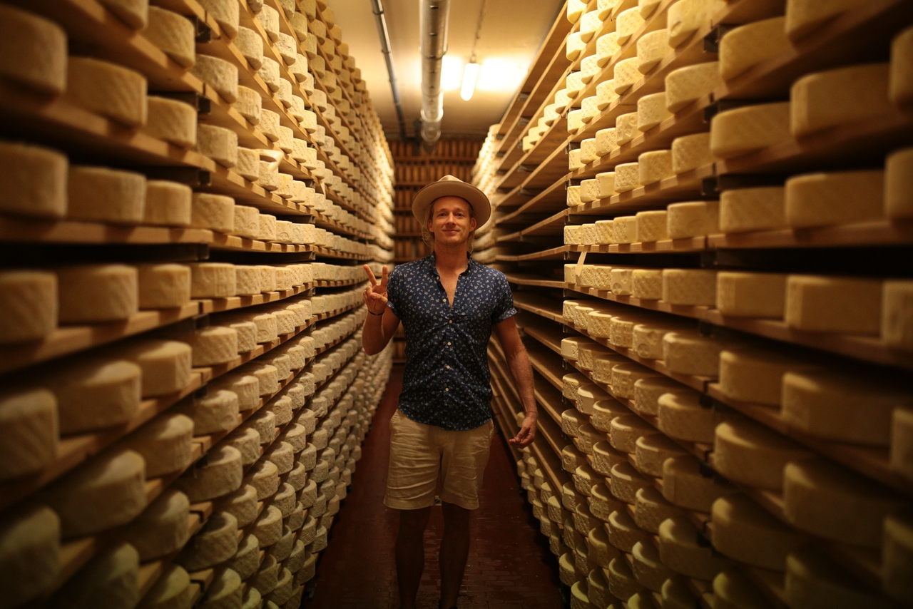 Guy Turland making a peace sign in a cheese room