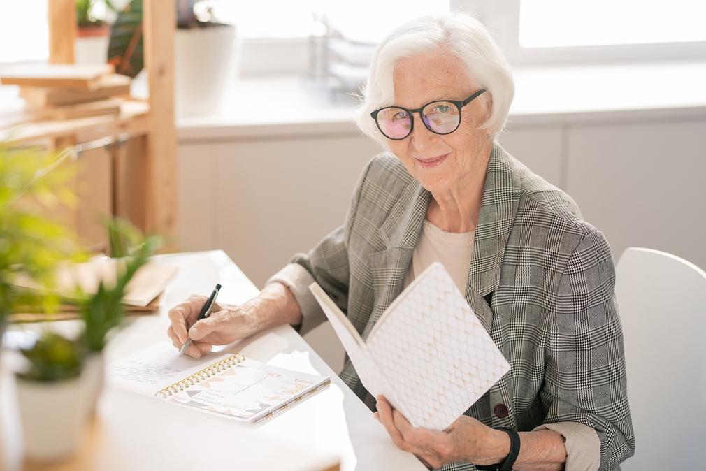 Elderly writing at her desk