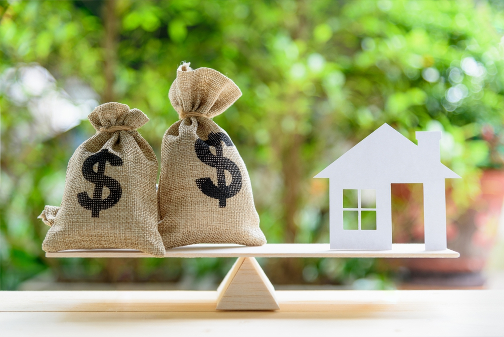 House and money bags balancing on a scale