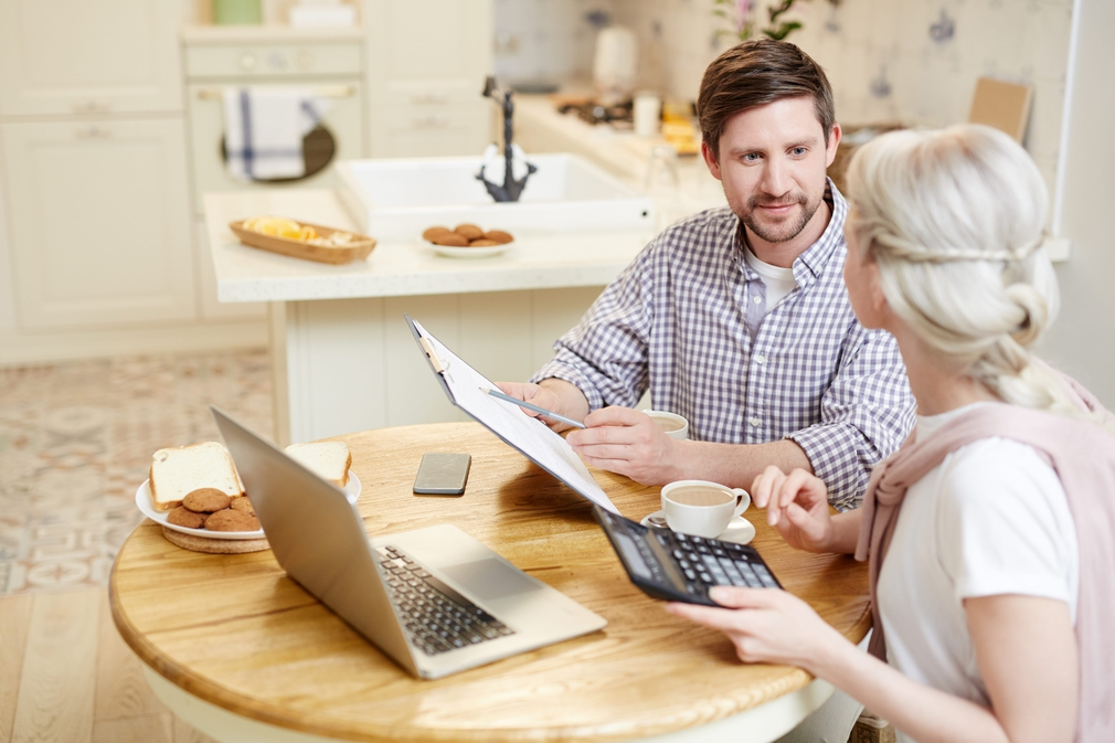 Couple using calculator while looking at documents