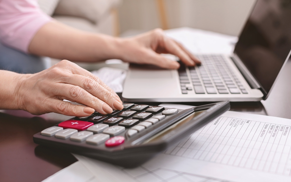Person using a calculator and laptop simultaneously