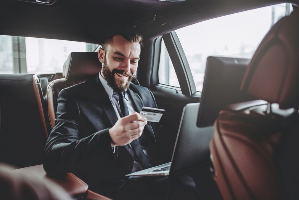 Businessman with credit card in the car