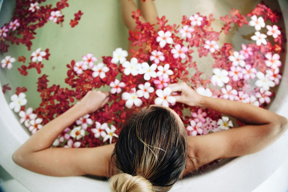 Woman soaking in a bath of flowers