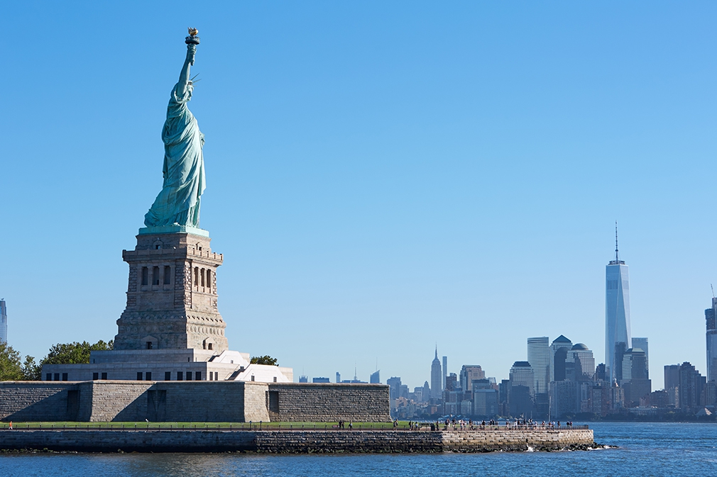 Visit the Statue of Liberty looking back to One World Trade Center in Manhattan