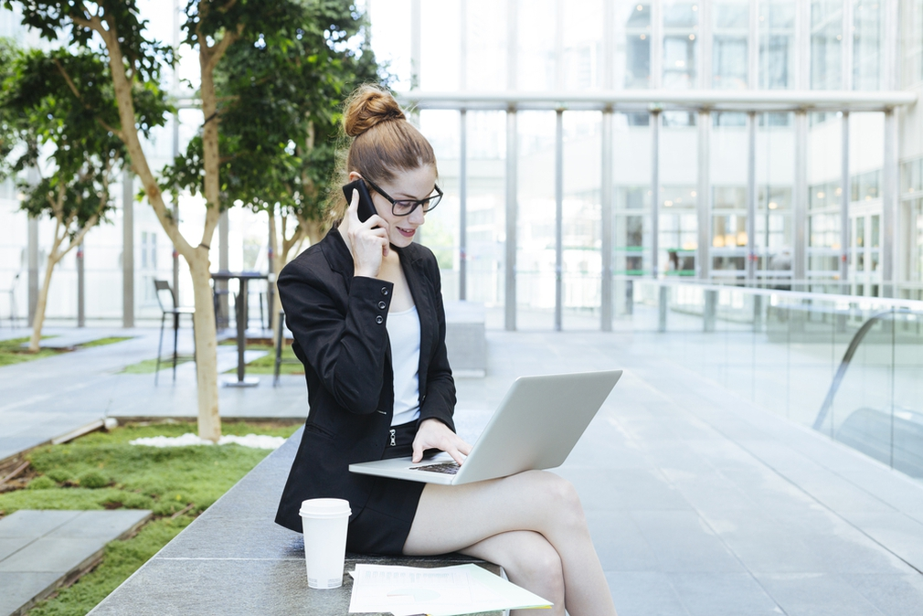 Woman on mobile phone while using laptop