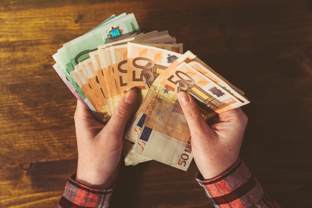 Female hands holding a large sum of money in Euros