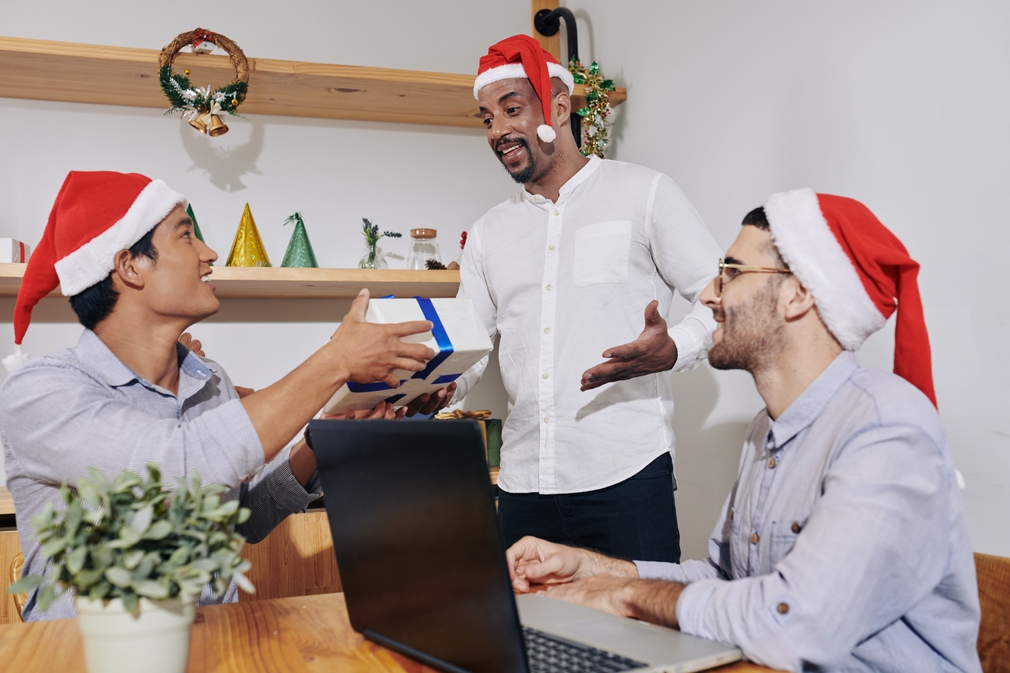 Male co-workers exchanging Christmas gifts