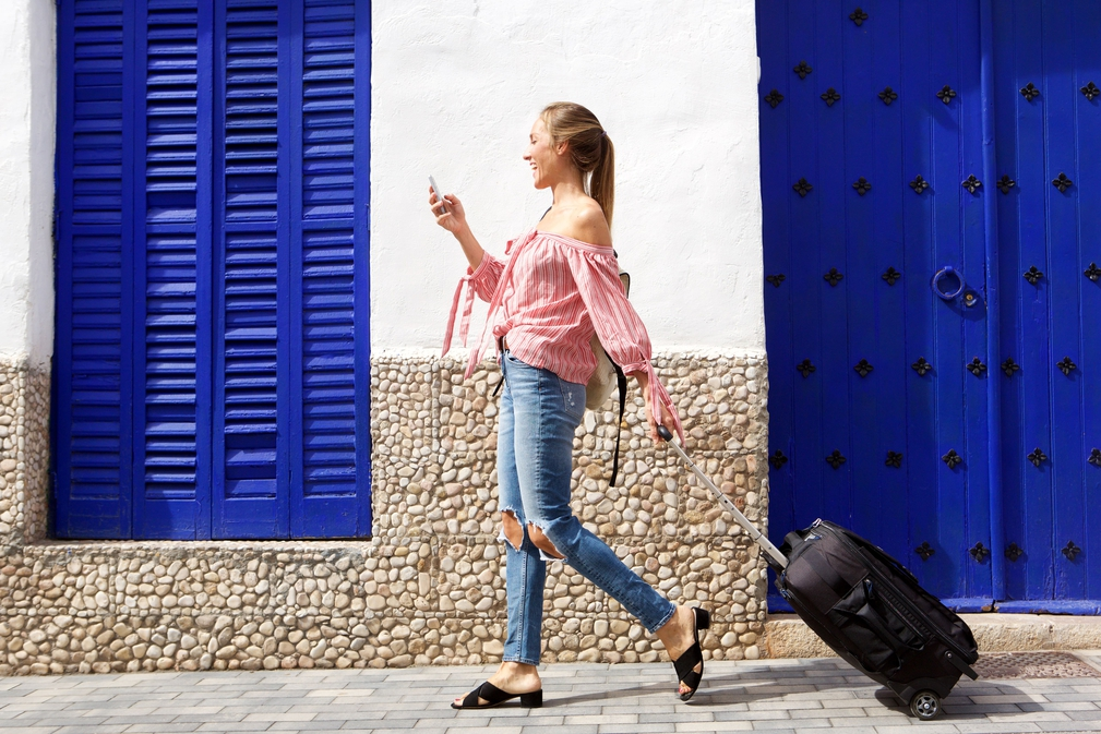 Young female traveller looking at mobile phone