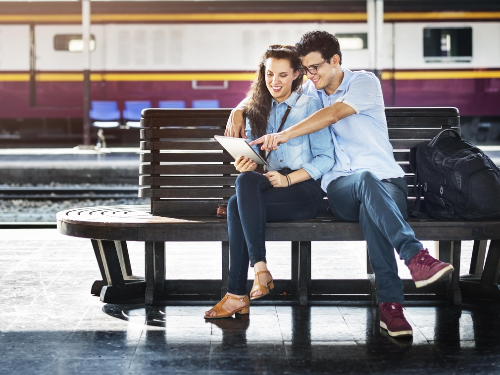 Couple sitting on a bench at a train station looking at a map